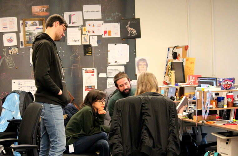 Four designers collaborating in the middle of several desks in front of a chalkboard with design ideas on it