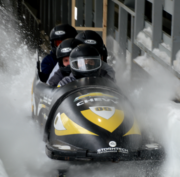 Three people bobsledding on a Mindgrub Adventure Club trip to Lake Placid