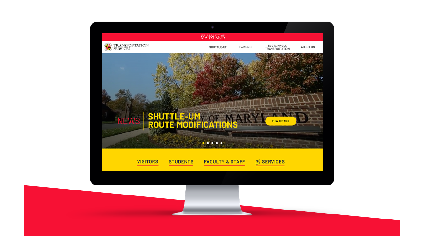 Desktop monitor with UMD DOTS Home Page displaying a large image of the campus sign
