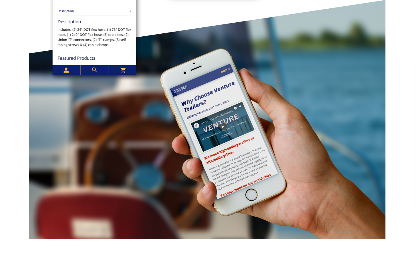 Someone on a boat holding a mobile phone with the new Venture Trailers website displayed