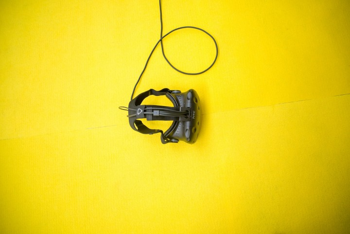 black virtual reality headset with power cord on a yellow background
