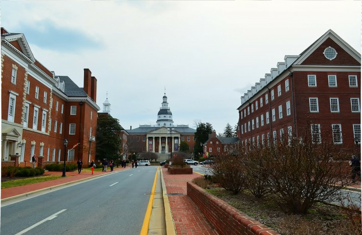 View from the middle of a road of the state capitol building in the center with the House of Delegates and Senate on either side.