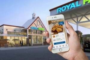 Royal Farms store in the background with a hand holding a smartphone displaying the Royal Farms app.